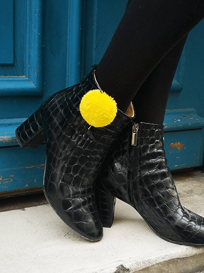 petits pompons jaunes sur chaussures noires