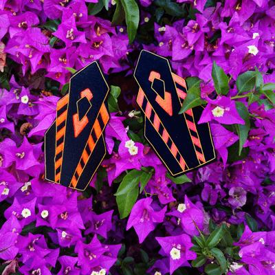paire d'epaulettes colette noires et neon sur des fleurs roses
