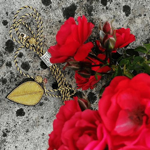bijou de gant Générale posé sur une pierre à coté d'une rose